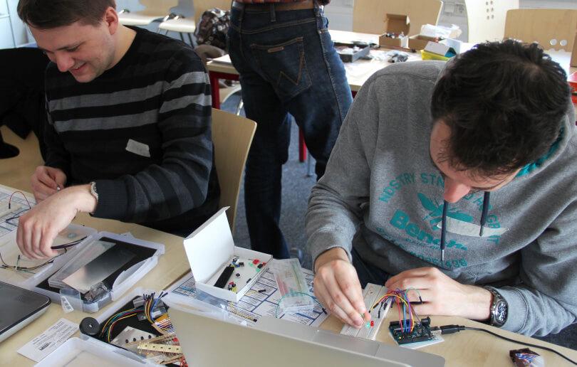 Auf dem Foto basteln zwei Männer an Mikrocontrollern.
