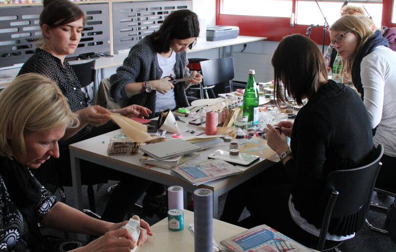 Das Foto zeigt mehrere Frauen, die mit einem Klebeband, Scheren und anderen Materialien im Makerspace der Bibliothek Köln.