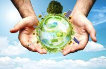 Auf dem Foto sieht man eine Weltkugel, die von zwei menschlichen Händen gehalten wird. Auf der Kugel sieht man sowohl Bäume, Gras und Sonnenblumen als auch Sonnenkollektoren und Windräder im Sinne eines ganzheitlichen und nachhaltigen Handelns.