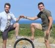 """Auf dem Foto stehen zwei Männer, Theo Rohfritsch und Simon Valdenaire vom Projekt """"Cycle of Water"""" , sich gegenüber. Je ein Bein steht auf einem Rad. Sie halten sich an den Händen und schauen in die Kamera."""