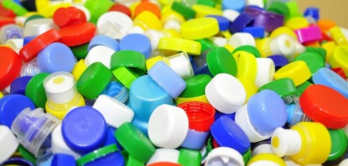 Auf dem Foto liegen viele farbige Plastikdeckel auf einem Haufen.