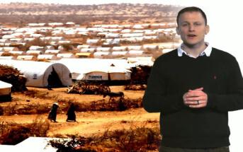 Daniel Otto, wissenschaftlicher Mitarbeiter bei infernum, steht vor einem Foto eines Flüchtlingscamps und spricht zum Zuschauer.