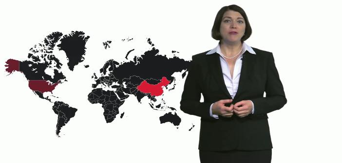 Auf dem Foto steht Angelika Oels vor einer Weltkarte und spricht zum Zuschauer. Die Länder sind dunkel vor weißem Hintergrund, einige sind rot hervorgehoben.