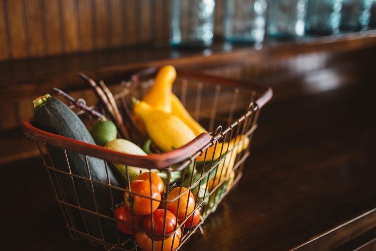 Das Foto zeiigt einen Warenkorb mit Gemüs. Die Künstlergruppe sortiert die Produkte nach der Nachhaltigkeit.